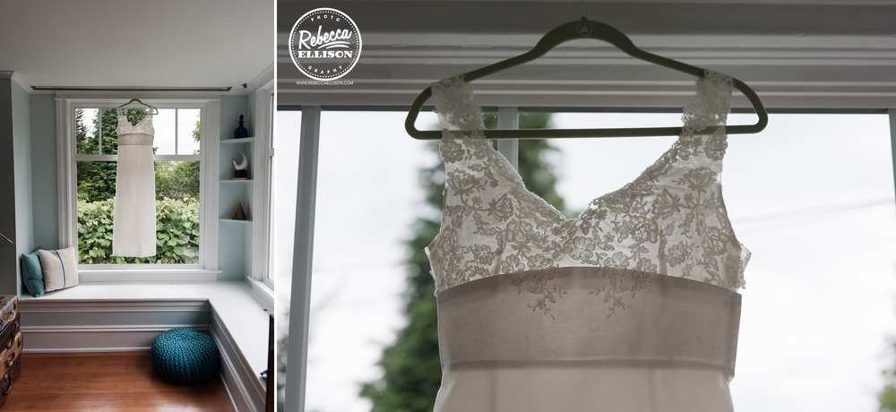 White wedding dress with lace detail hangs in a window photography by Rebecca Ellison