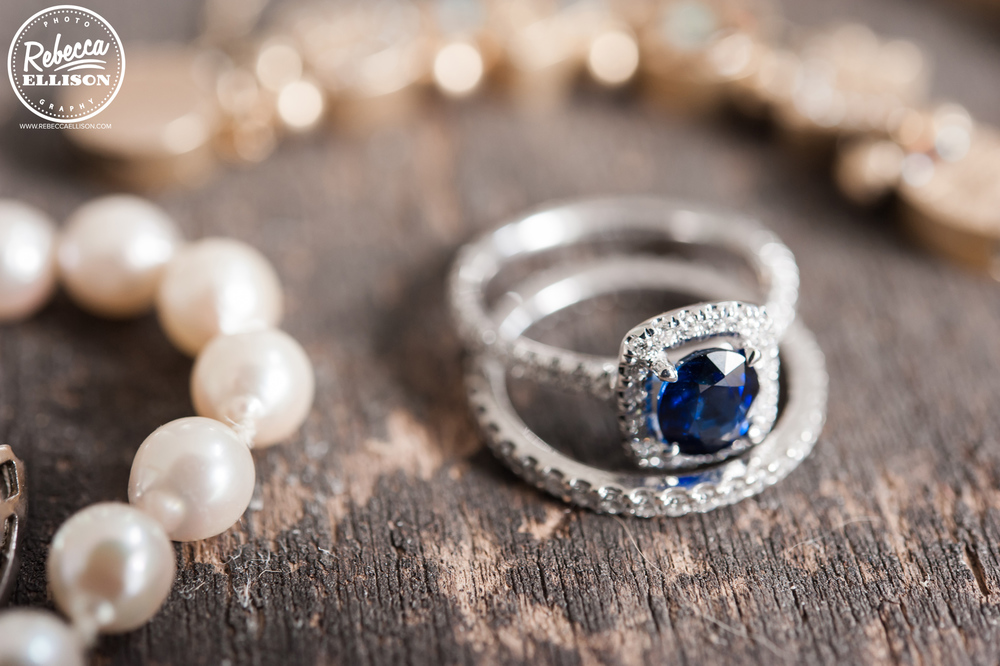 Bride's rings and pearl necklace sit on a rough wooden floor photographed by Rebecca Ellison photography