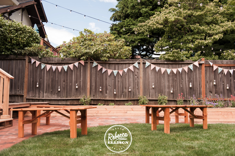 An intimate backyard wedding space is decorated with penant banners, lights and picnic tables photographed by Rebecca Ellison photography
