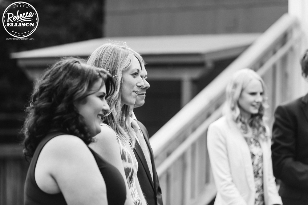 Bridesmaids watch during a weddinf ceremony at an intimate backyard wedding photographed by Seattle wedding photographer Rebecca Ellison