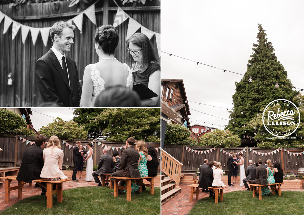 Wedding guests sit on wooden picnic benches at an intimate backyard wedding featuring light strings and penant banners photographed by Seattle wedding photographer Rebecca Ellison