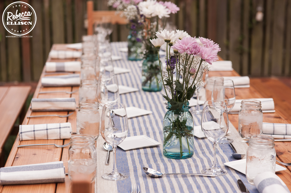Dinner table at a DIY intimate backyard wedding featuring picnic tables, blue and white table runners and DIY flowers photographed by seattle wedding photographer Rebecca Ellison