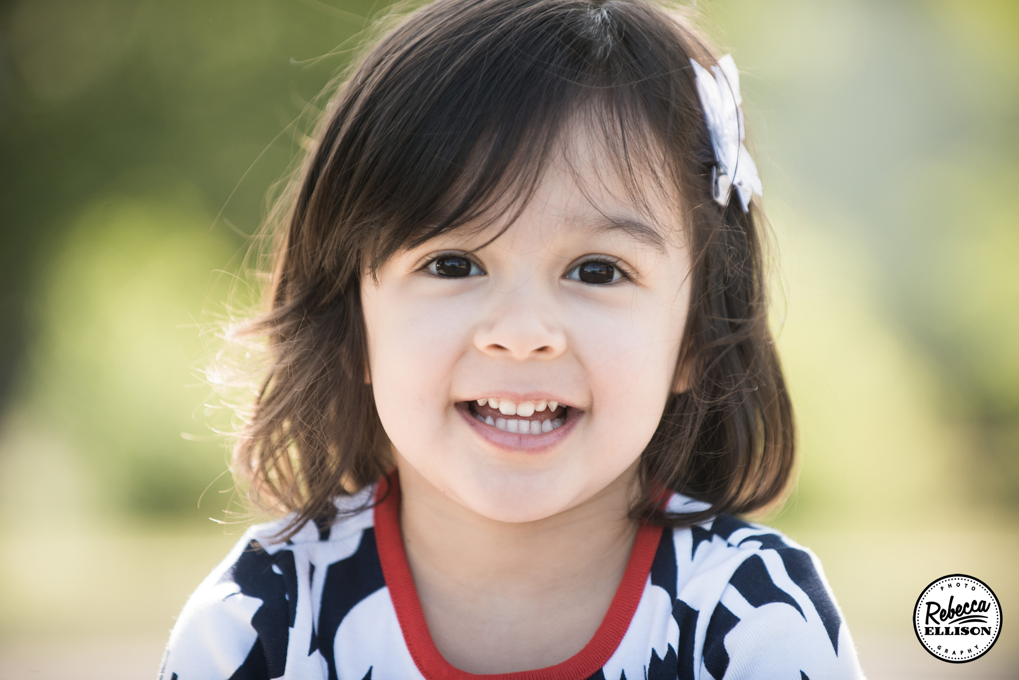 Beautiful litle girl smiles for the camera during an Kirklad Family portraits by Rebecca Ellison Photography
