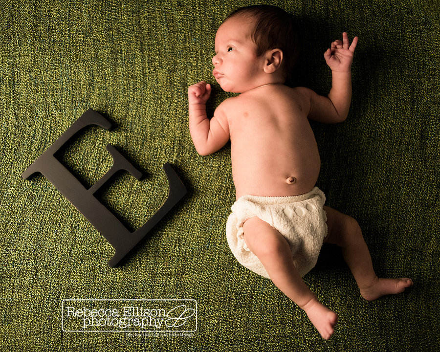 Indoor newborn portraits of a baby on a green rug next to a wooden letter E, his first initial, photographed by Seattle newborn photographer Rebecca Ellison