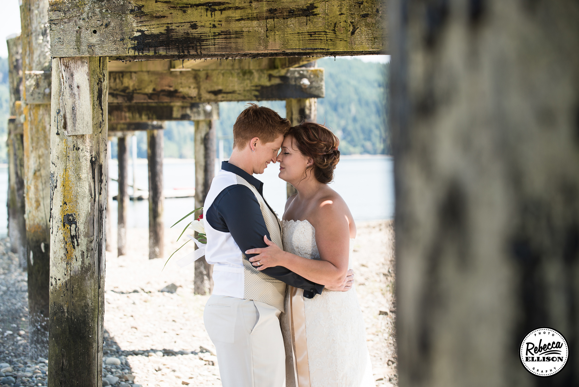 Beachfront wedding portraits of a same sex couple standing under a dock photographed by Rebecca Ellison Photography