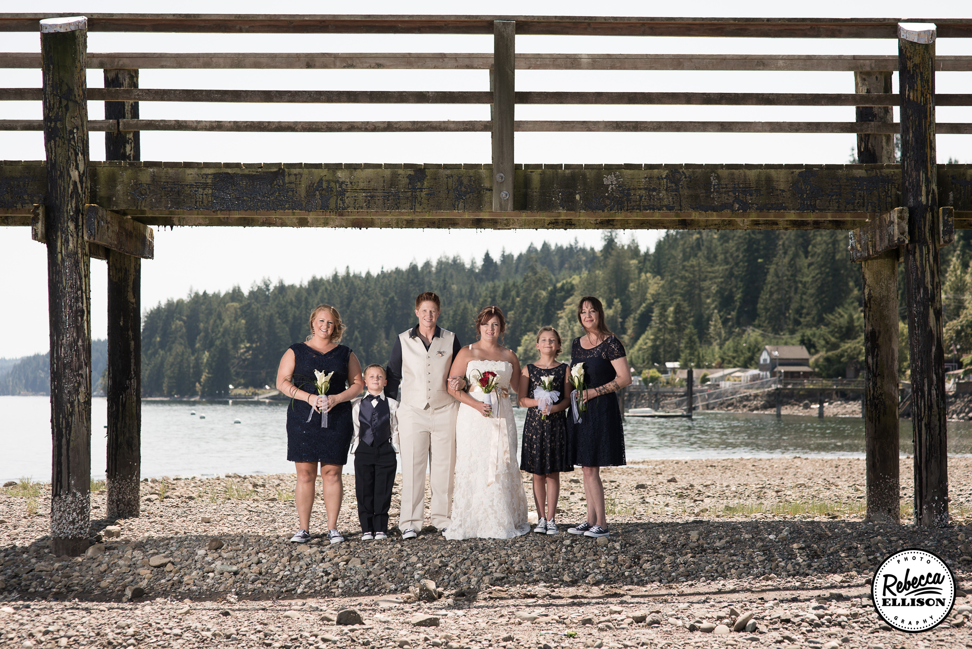 Wedding party portraits under a wooden dock at a beachfront wedding featuring Navy blue dresses and a white belted wedding dress