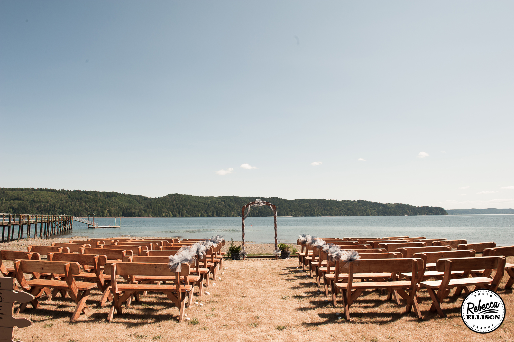 Hoodsport Beach Club wedding venue featuring a sandy beach, wooden benches and an archway overlooking the water