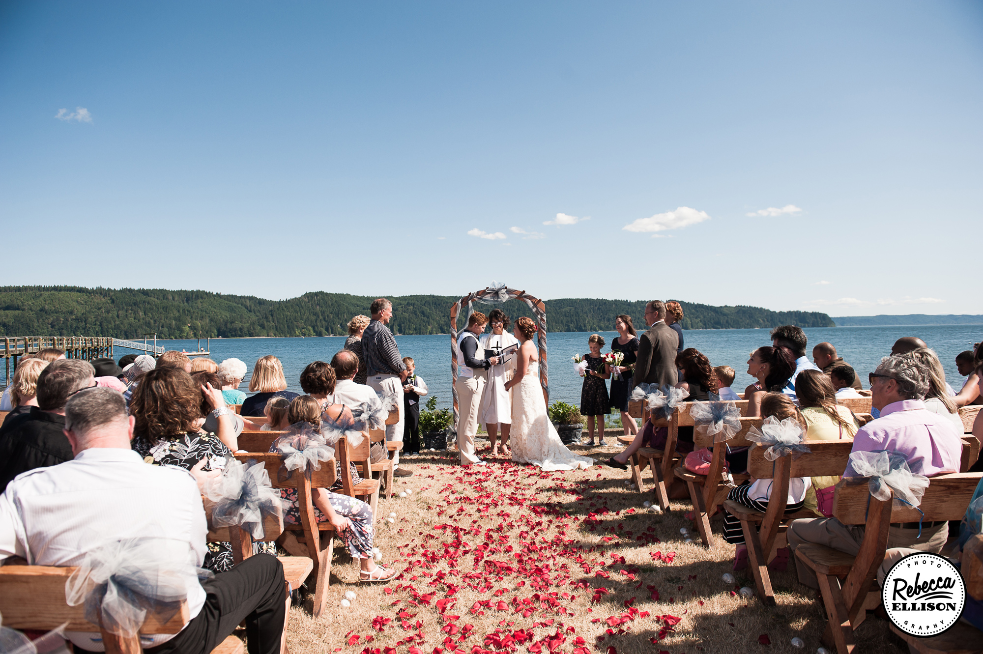 Beachfront wedding in Hoodsport, Wa featuring a flower petals in the sand, a wooden arch and view of the ocean photographed by Rebecca Ellison Photography