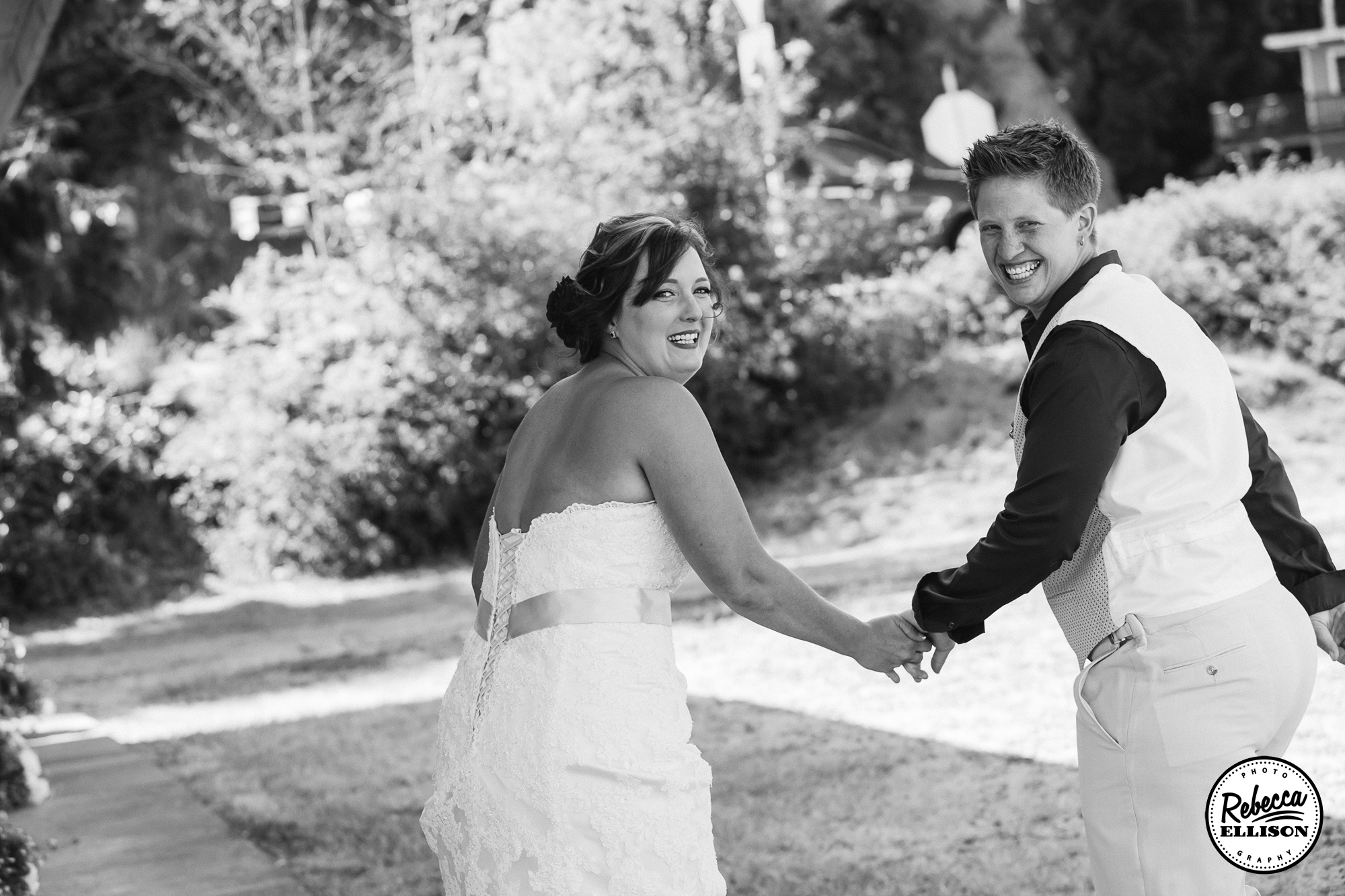 Same Sex couple smiles after their wedding ceremony in Outdoor black and white wedding portraits photographed by Seattle wedding photographer Rebecca Ellison