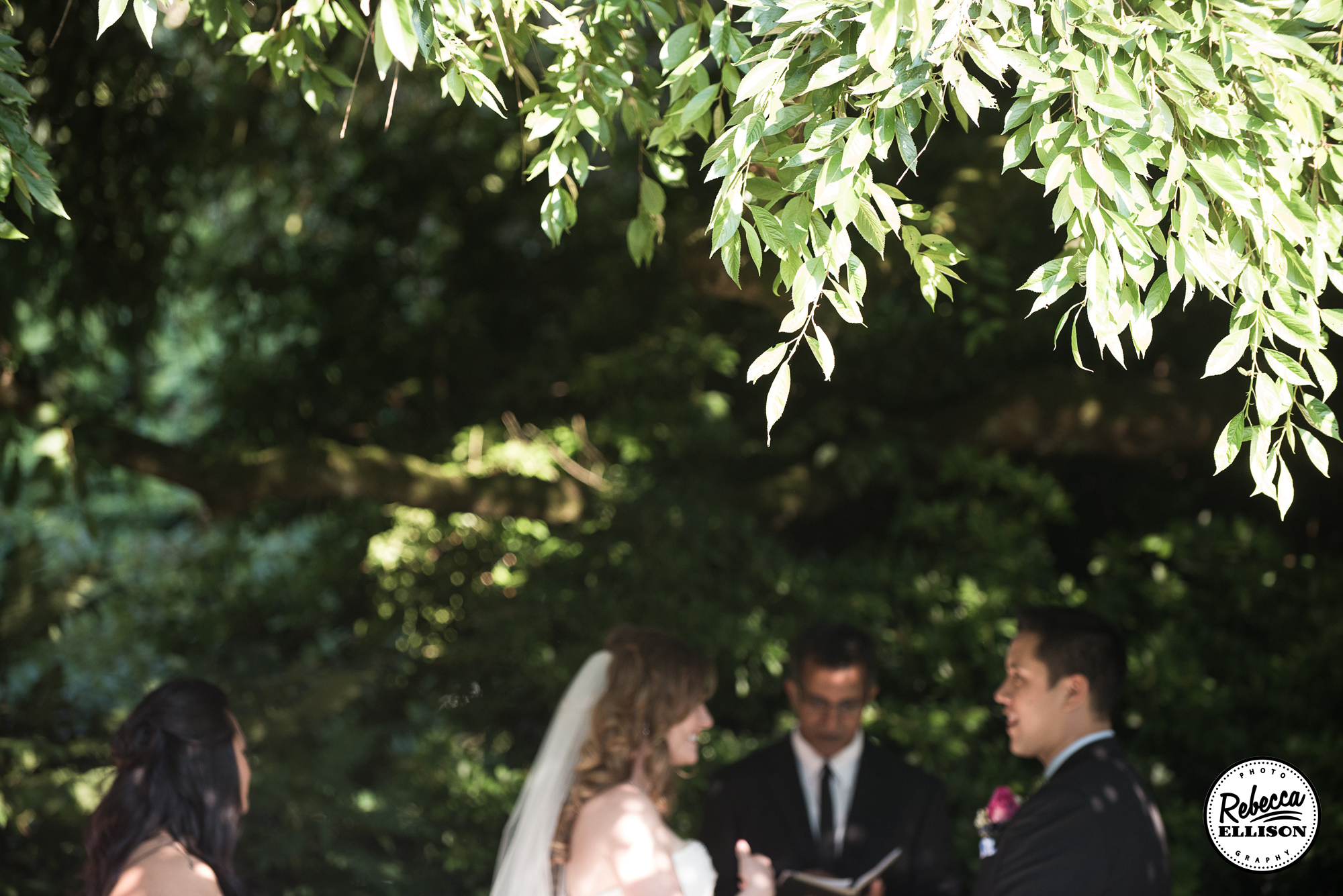 Bride and groom during their wedding ceremony under the trees at their Parsons Garden wedding photographed by Seattle wedding photographer Rebecca Ellison
