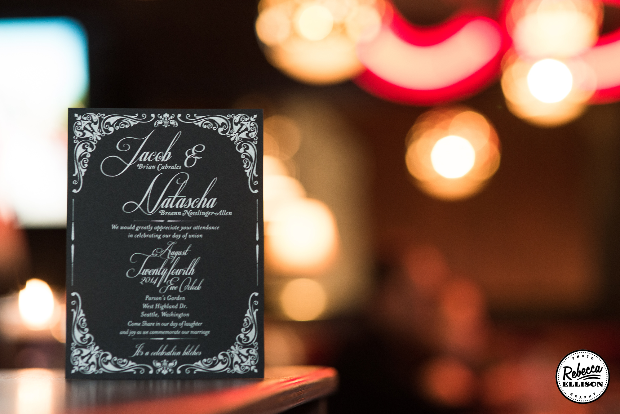 Black and white wedding invitation with neon signs in the background photographed by Seattle wedding photographer Rebecca Ellison