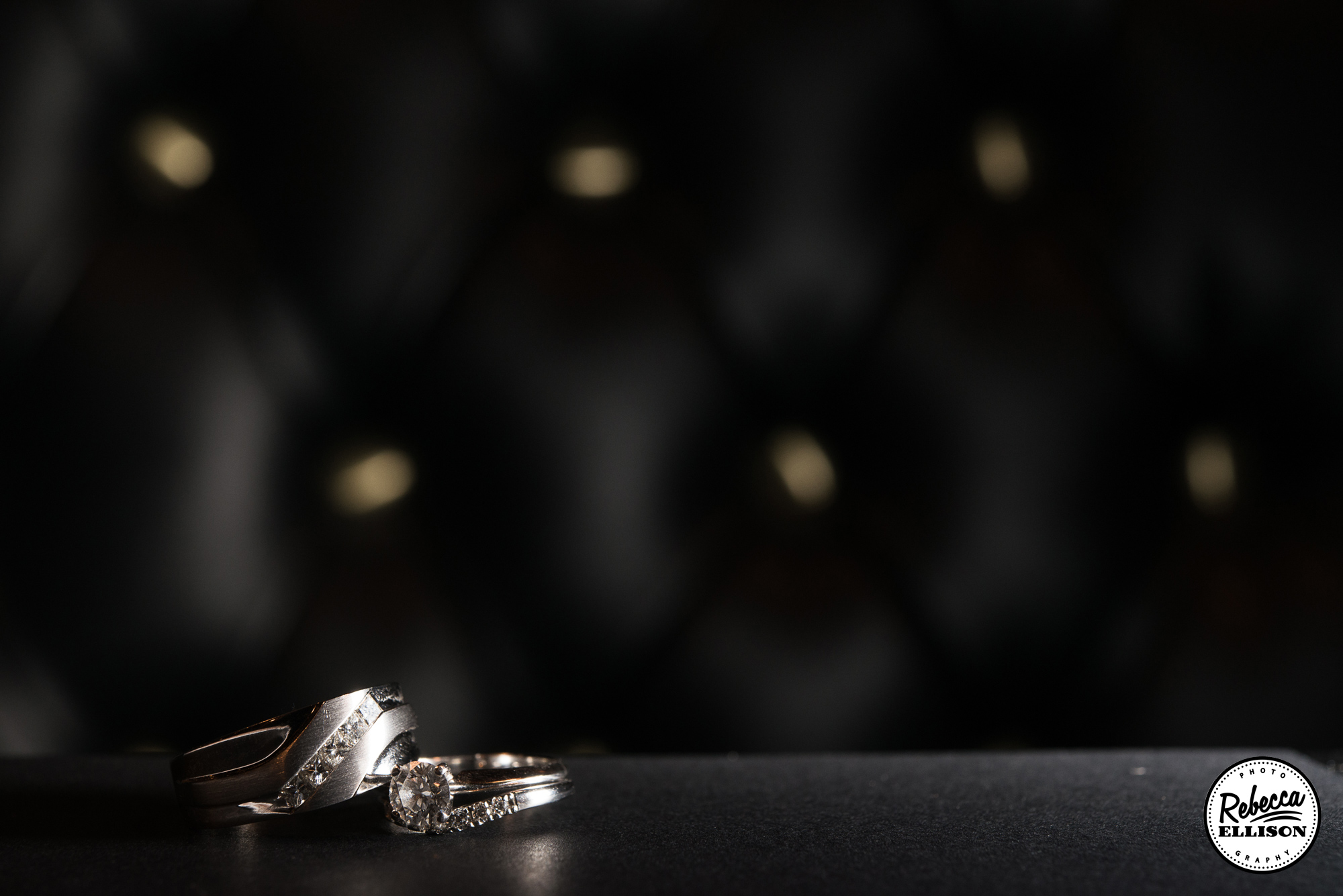 Wedding rings against a black leather background photography by Rebecca Ellison