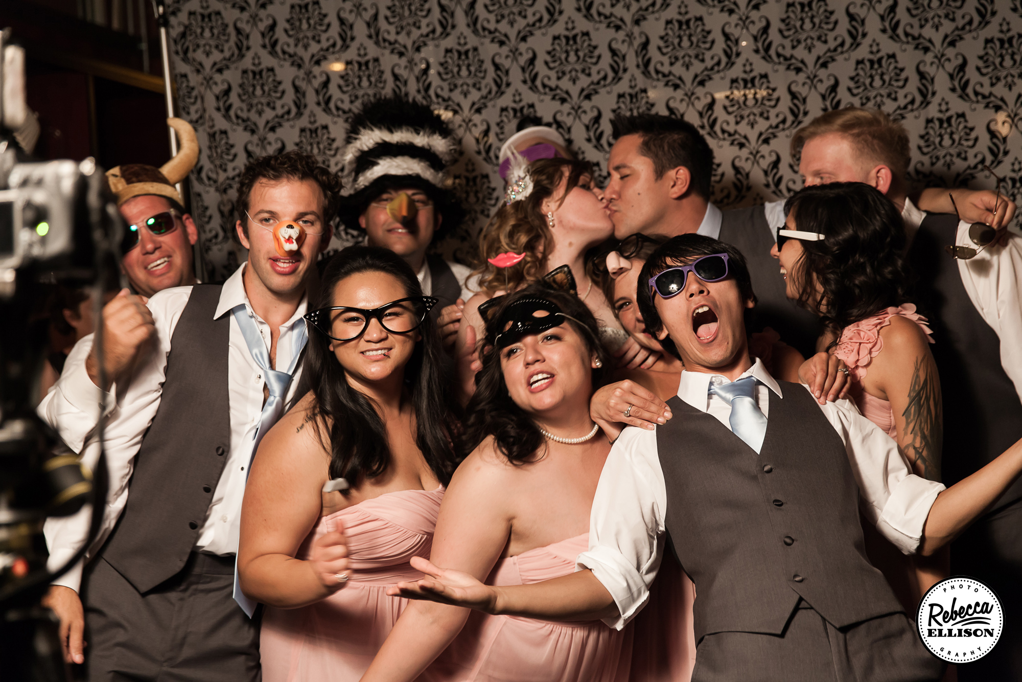 Wedding Party poses at a photo booth with silly props featuring pale pink dresses and grey suits photographed by Seattle wedding Photographer Rebecca Ellison