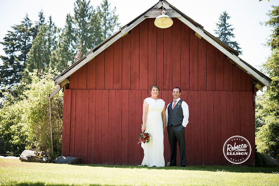 bride and groom stand in front of red barn at farm kitchen poulsbo photographed by Seattle wedding photographer Rebecca Ellison