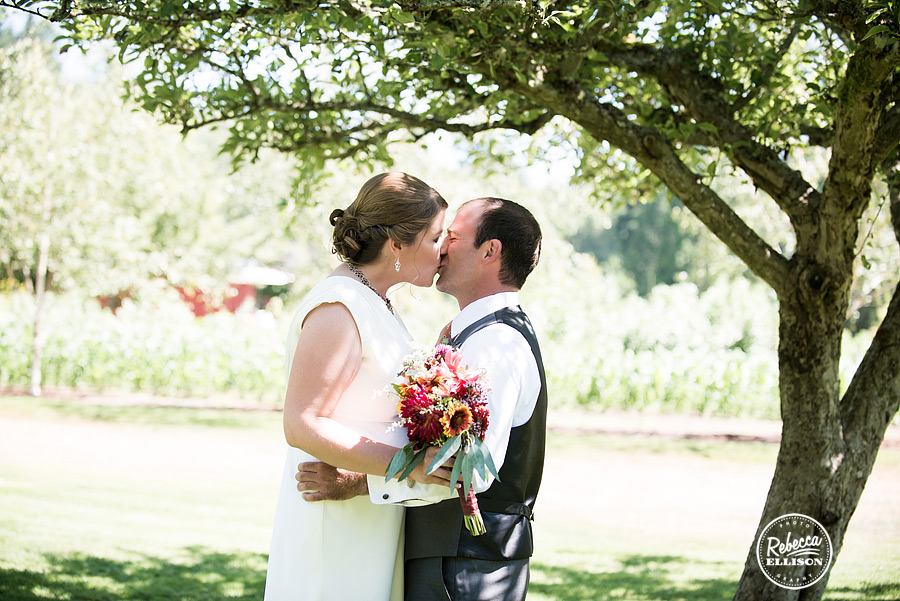 bride and groom kiss at first site under apple orchard trees at farm kitchen wedding in poulsbo photographed by Seattle wedding photographer Rebecca Ellison