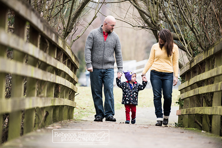 A family walks on a wooden bridge at the park on a fall day during family portraits photographed by Seattle toddler photographer Rebecca Ellison