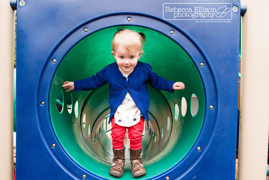 Two year old in a playground tunnel at the park photographed by Seattle toddler photographer Rebecca Ellison