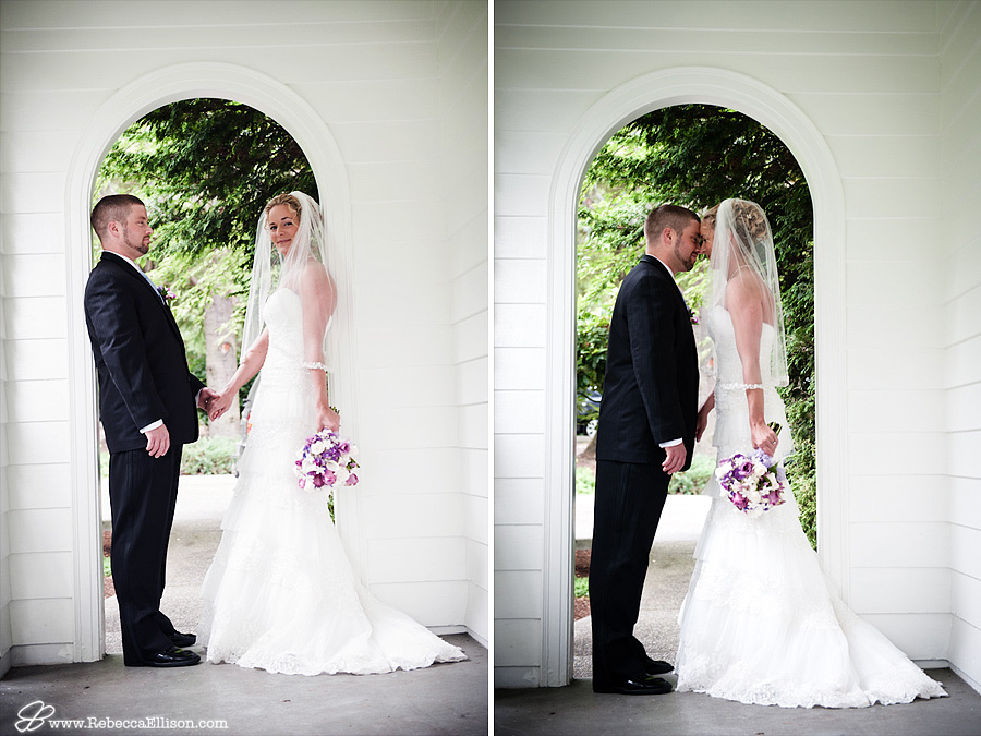 Bride and groom stand in an arched doorway featuring a white lace tiered wedding dress from Bridal and Veil photographed by Bothell wedding photographer Rebecca Ellison