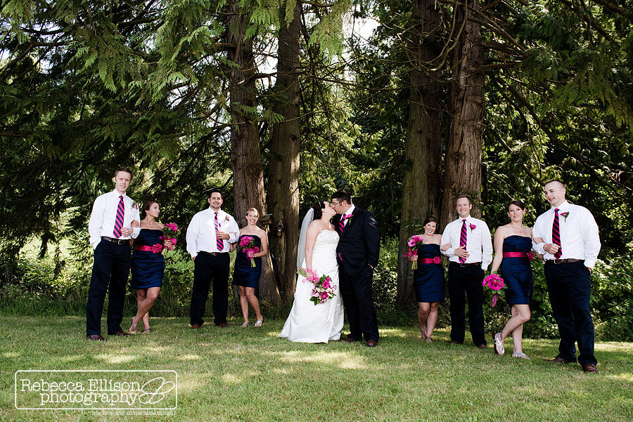 Outdoor summer wedding at Tazer valley Farm featuring Navy blue and Pink bridesmaids dresses and a white strapless wedding gown in a forest setting photographed by Rebecca Ellison Photography
