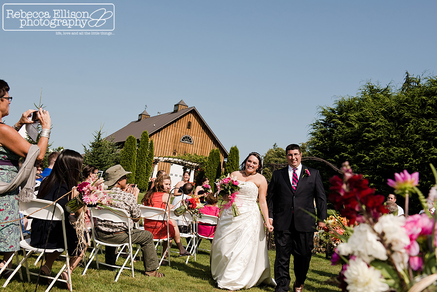 Bride and groom walk down the aisle after their outdoor wedding ceremony photographed by Rebecca Ellison Photography