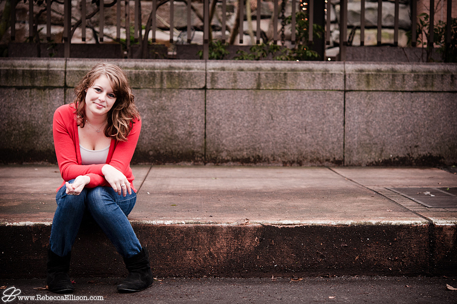 Urban outdoor senior portraits featuring a grey cement landscape and a bright orange sweater photographed by Seattle Senior Portrait photographer Rebecca Ellison