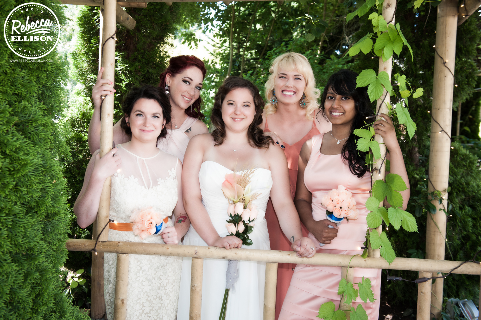 Bride and her bridesmaids at a peach and blue wedding at snohomish wedding venue Jardin Del Sol featuring silk flowers photographed by Rebecca Ellison Photography