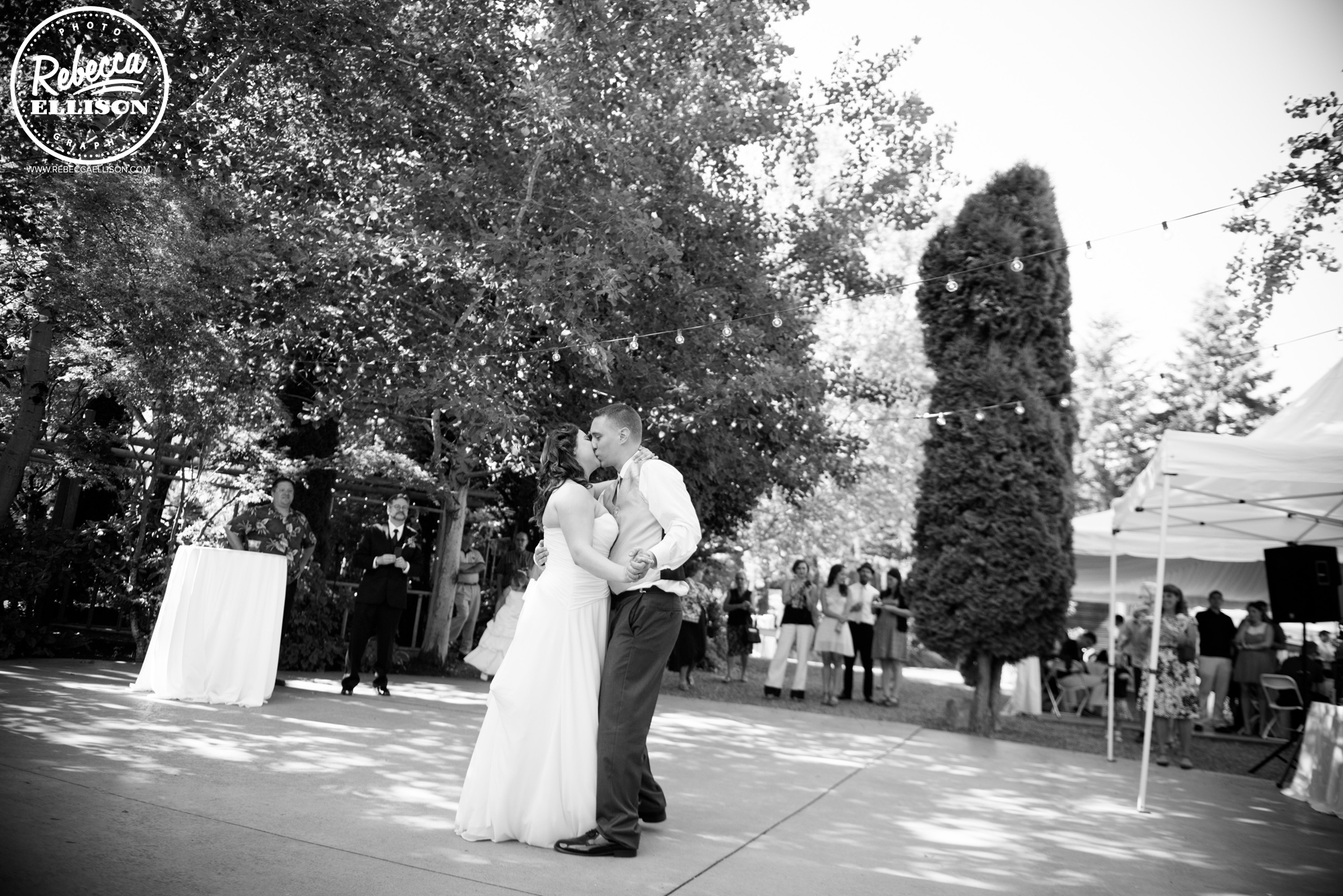 Bride and groom dance at their outdoor wedding featuring a white strapless wedding dress and hanging lights photographed by Seattle wedding photographer Rebecca Ellison