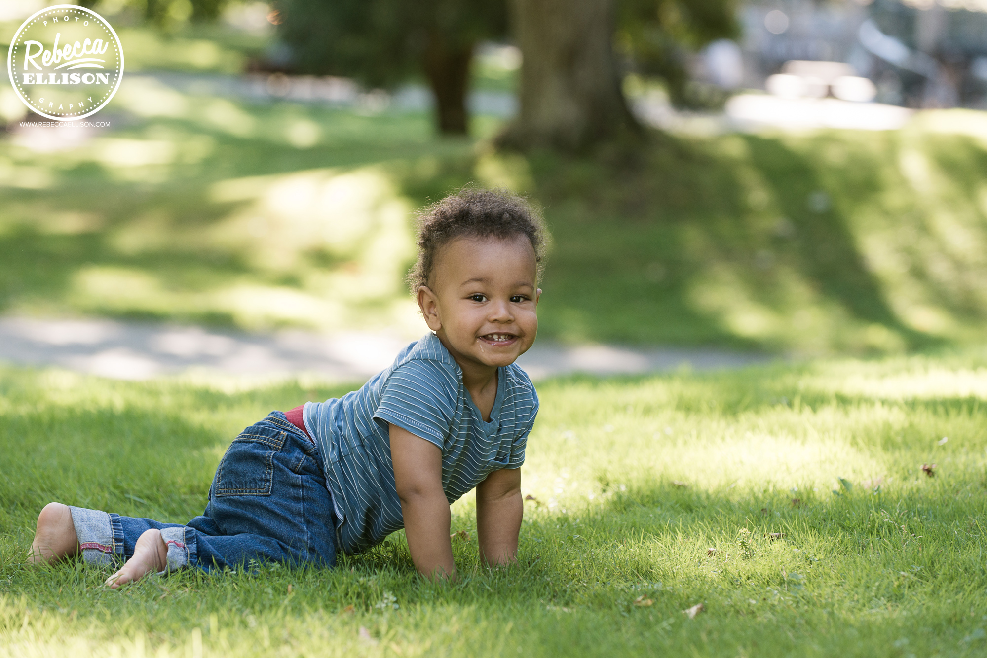 One year old boy crawls in the grass during an outdoor portrait session with Tacoma Child Photographer Rebecca Ellison