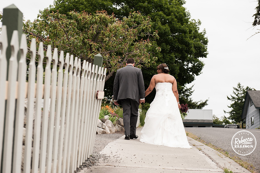 Bride and groom walk down the sidewalk in Friday harbor for their outdoor wedding portraits photographed by Seattle wedding photographer Rebecca Ellison wedding dress by Lainee Meg Bridal