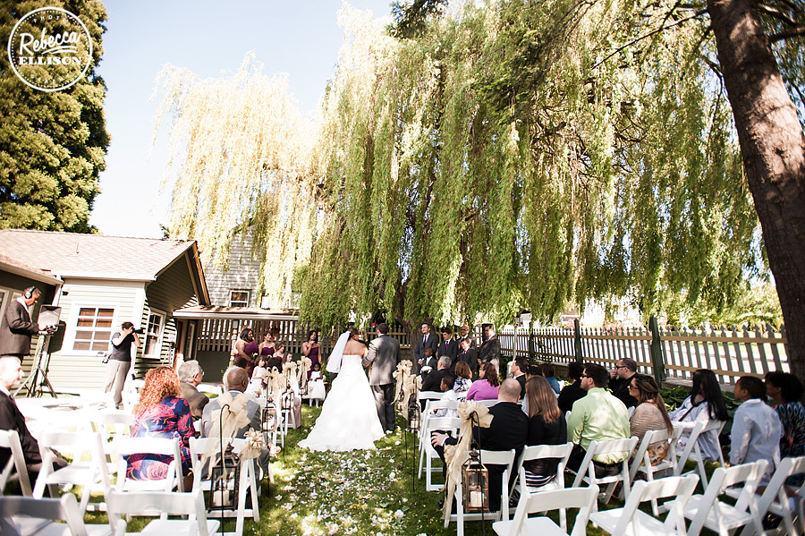 Intimate wedding ceremony under a weeping willow at Tucker House Inn in Friday harbor photographed by Seattle wedding photographer Rebecca Ellison