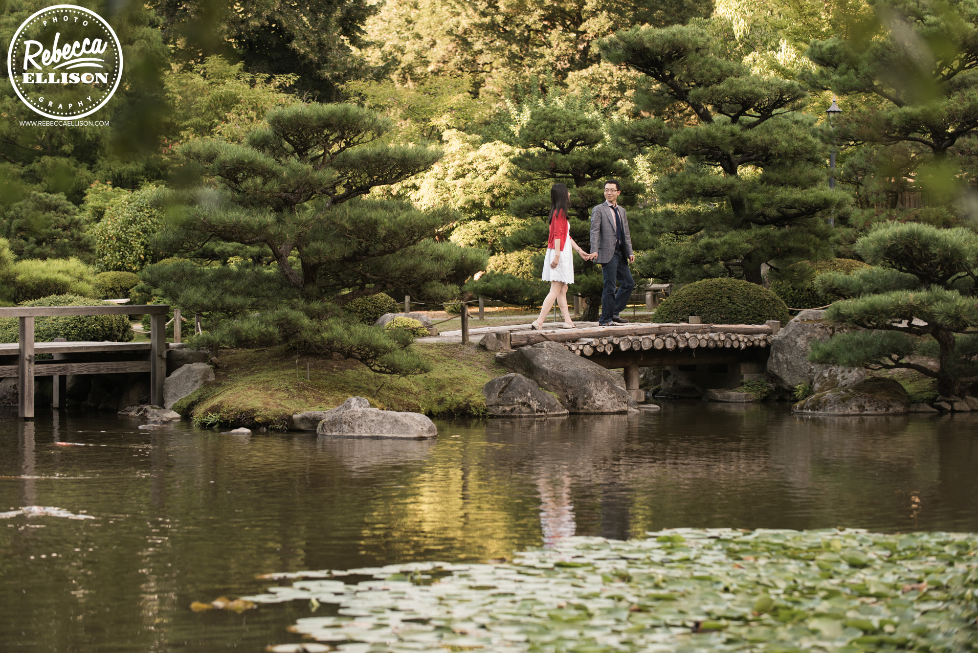 An engaged couple walks across a bridge at University of Washington's Japanese Gardens photographed by University of Washington Engagement Photographer Rebecca Ellison