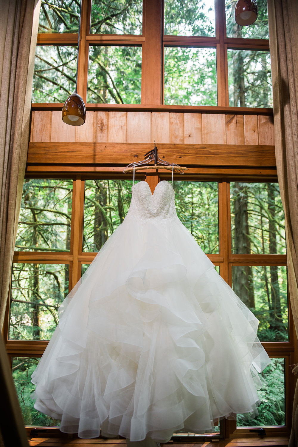 ruffled strapless wedding dress hanging from a tree house