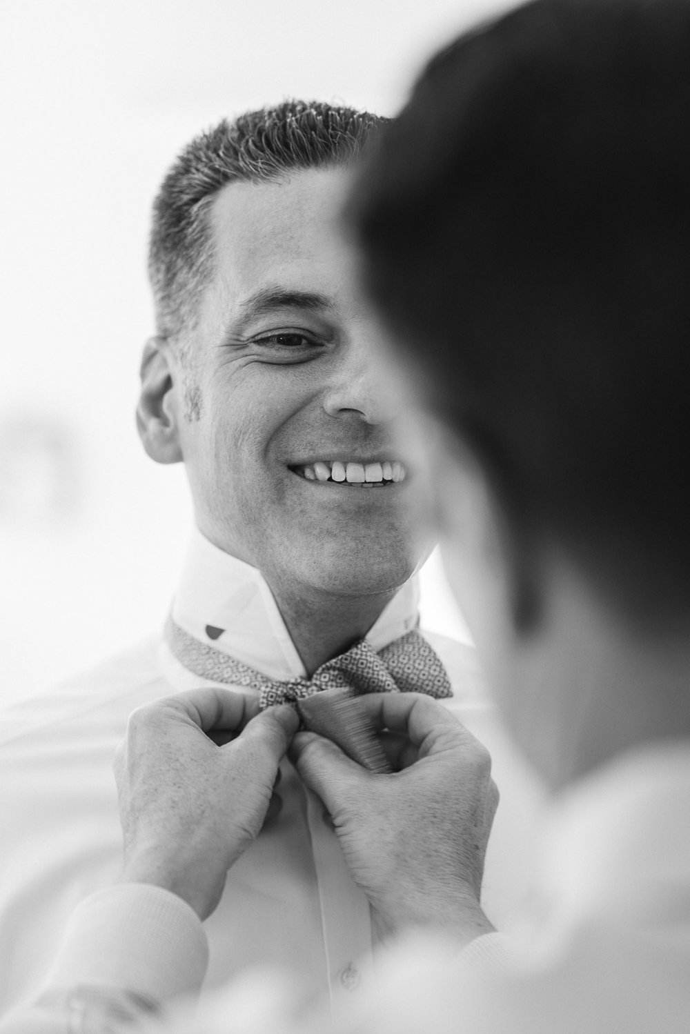 Groom having bowtie tied before his wedding. 