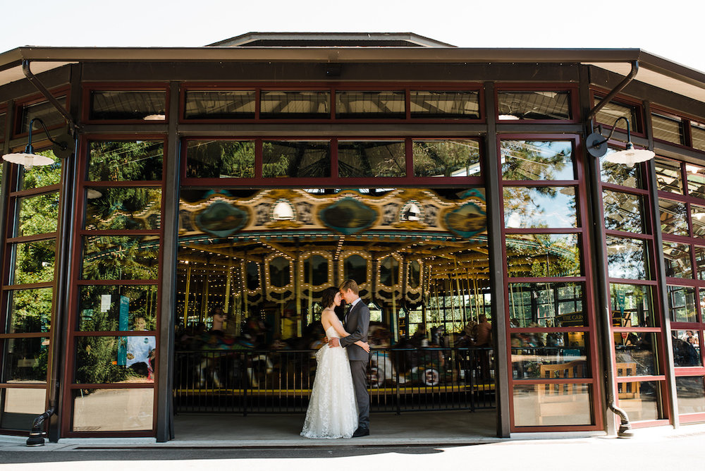 Bride and groom at Woodland Park Zoo Wedding in front of the carousel photographed by Seattle Wedding Photographer Rebecca Ellison Photography. www.RebeccaEllison.com