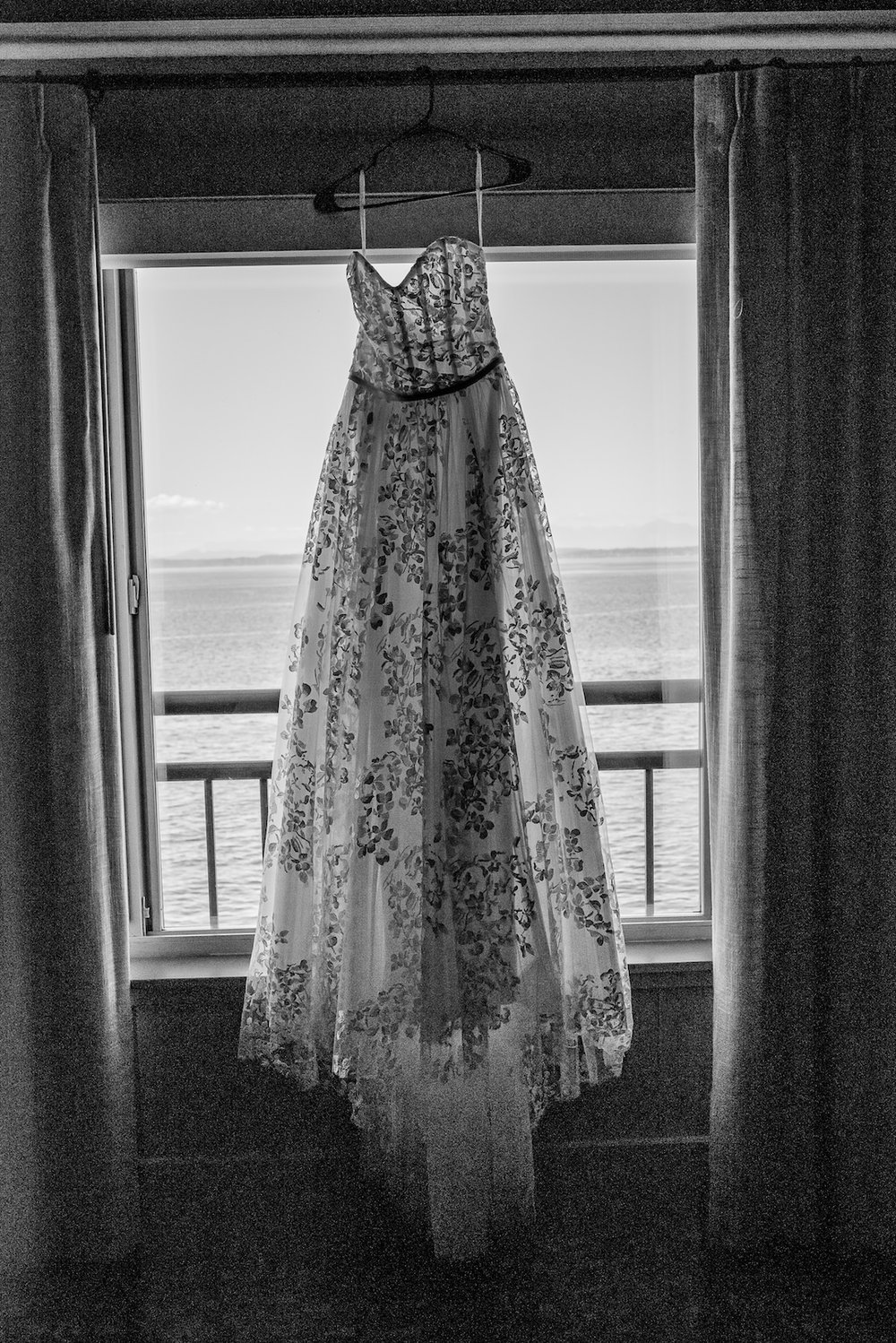 Lace dress hanging in the window with a waterfront view at Woodland Park Zoo Wedding photographed by Seattle Wedding Photographer Rebecca Ellison Photography. www.RebeccaEllison.com