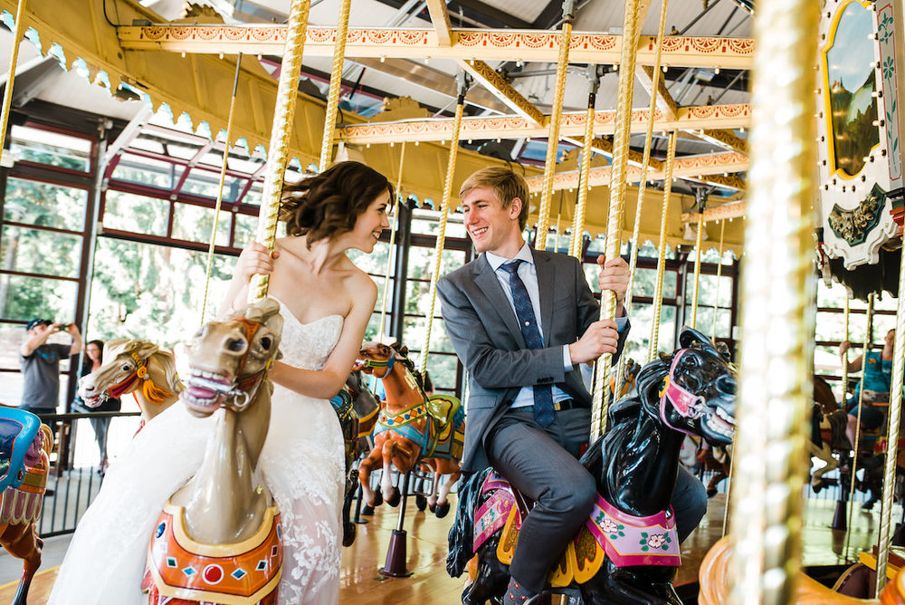 Bride and groom riding the carousel at Woodland Park Zoo Wedding photographed by Seattle Wedding Photographer Rebecca Ellison Photography. www.RebeccaEllison.com