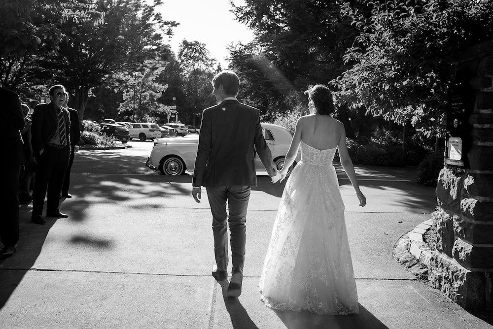 Bride and groom leaving their Woodland Park Zoo Wedding in a white classic car photographed by Seattle Wedding Photographer Rebecca Ellison Photography. www.RebeccaEllison.com
