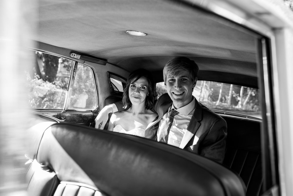 Bride and groom in a classic car at a Woodland Park Zoo Wedding photographed by Seattle Wedding Photographer Rebecca Ellison Photography. www.RebeccaEllison.com