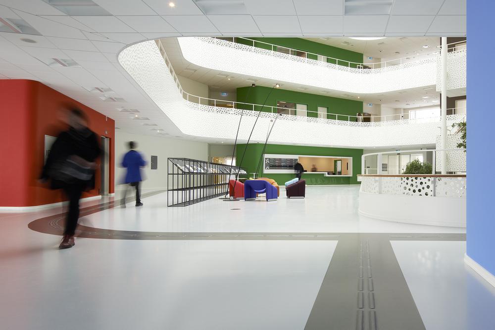 Interiør fra det store Atrium i husets kerne. Akustikken er tilrettelagt, så man kan fornemme bevægelsen fra atriet til længerne i det stjerneformede hus via lyden. Foto: Martin Schubert