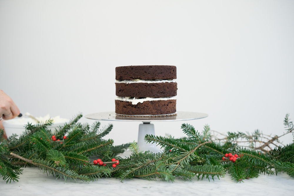 RIch Chocolate brownie cake layered with fluffy italian meringue buttercream, and peppermint chocolate bark