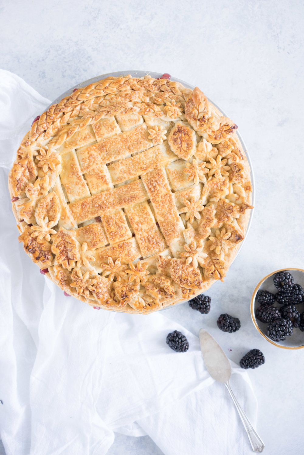 Apple and blackberry pie with herringbone lattice, braids, and pie stamps