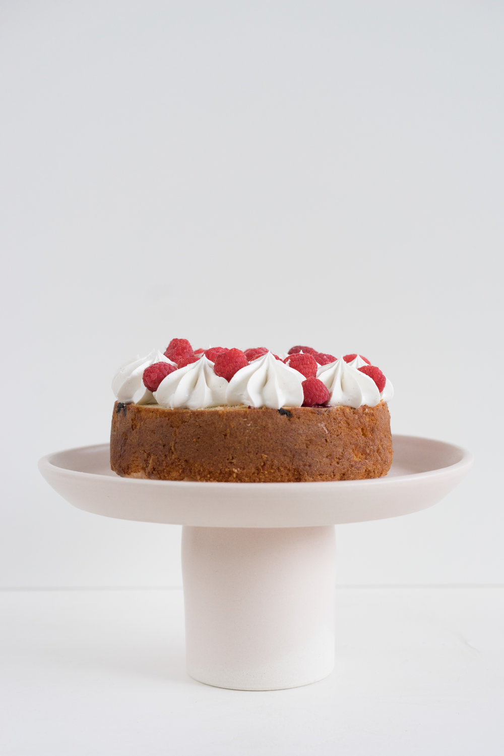 Raspberry and Almond cake - a perfectly dense almond meal cake, lightly scented with lemon, and with a layer of fresh raspberries baked into each layer. Layered with vanilla swiss meringue buttercream and more fresh raspberries. perfect for Mother's day or any other special occasion.