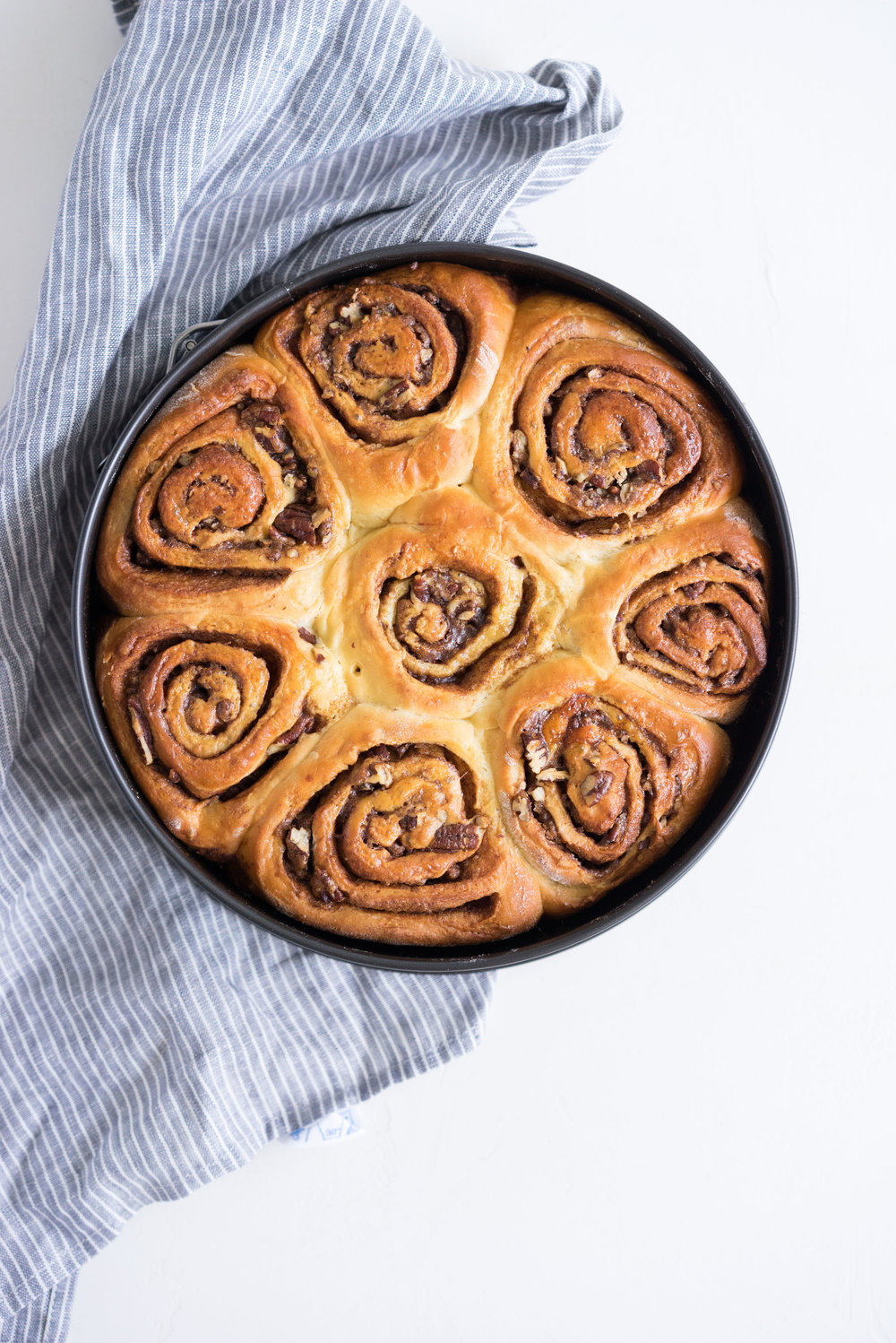Overnight Cinnamon Buns with Cream Cheese Frosting - Pillowy brioche that is prepared the night before, then rolled out the next morning, stuffed with cinnamon sugar and toasted peanuts, then smothered in cream cheese frosting while still warm. The perfect treat to please a crowd.