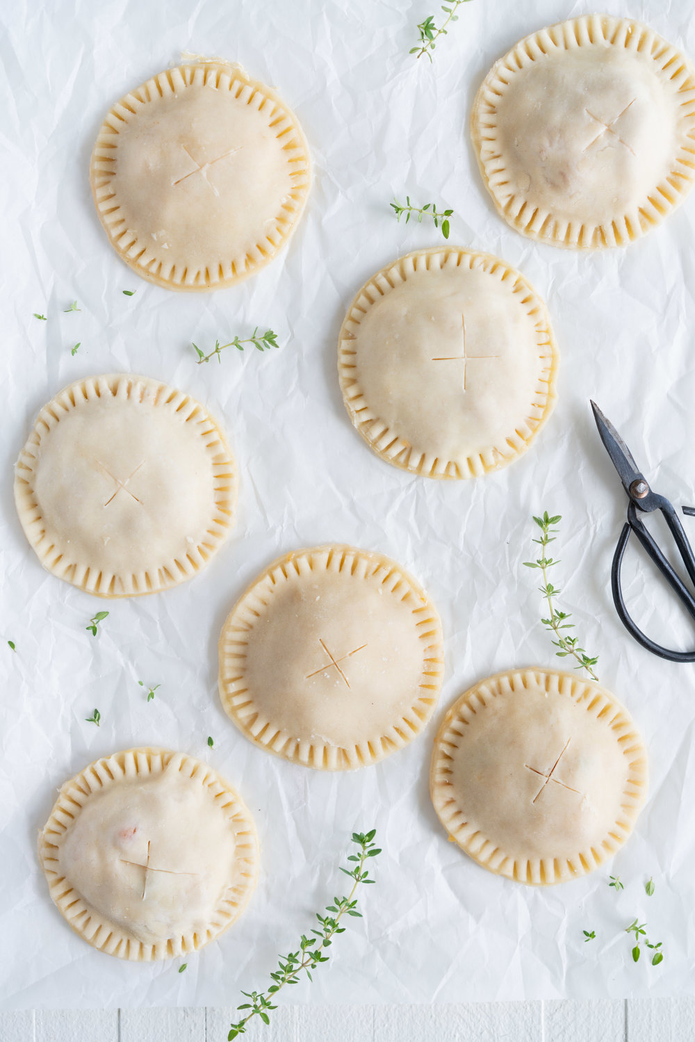 Peach and Thyme Hand pies - sweet, ripe peaches are enveloped in a tender flaky pie crust, and enhanced with the delicate flavour of thyme. #handpies #peachpies #pie #baking #peach #thyme