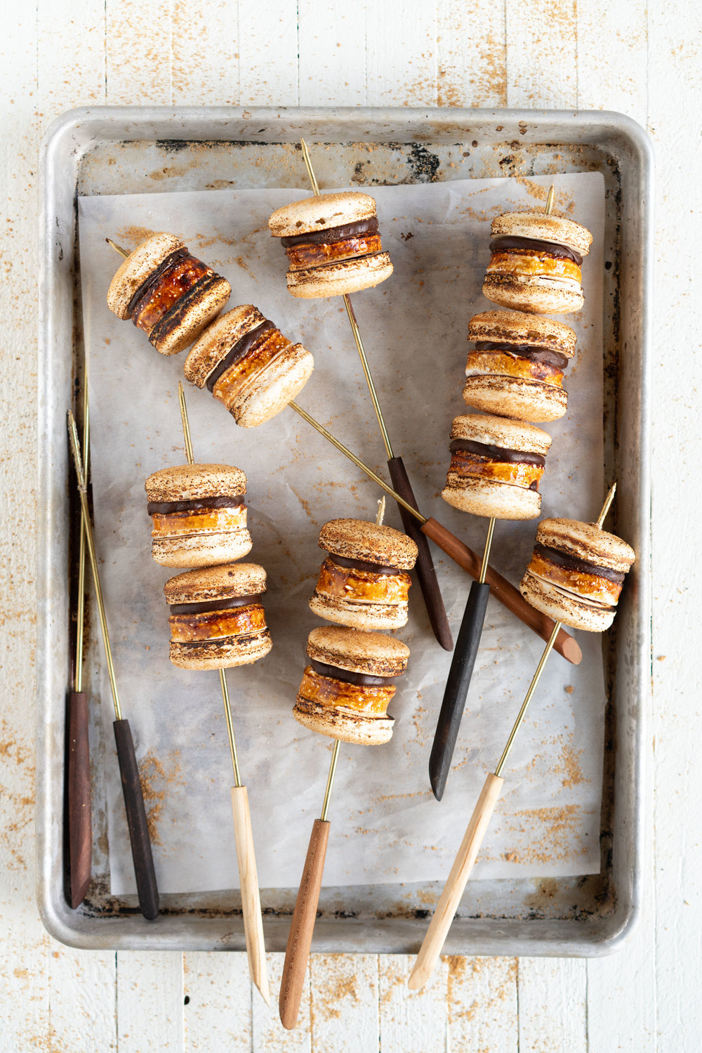 S'mores Macarons - Graham Cracker Shell, Toasted marshmallow disc, and silky dark chocolate ganache. The perfect campfire inspired bite without having to leave the confines of your kitchen. #smores #macarons #frenchmacarons #marshmallow