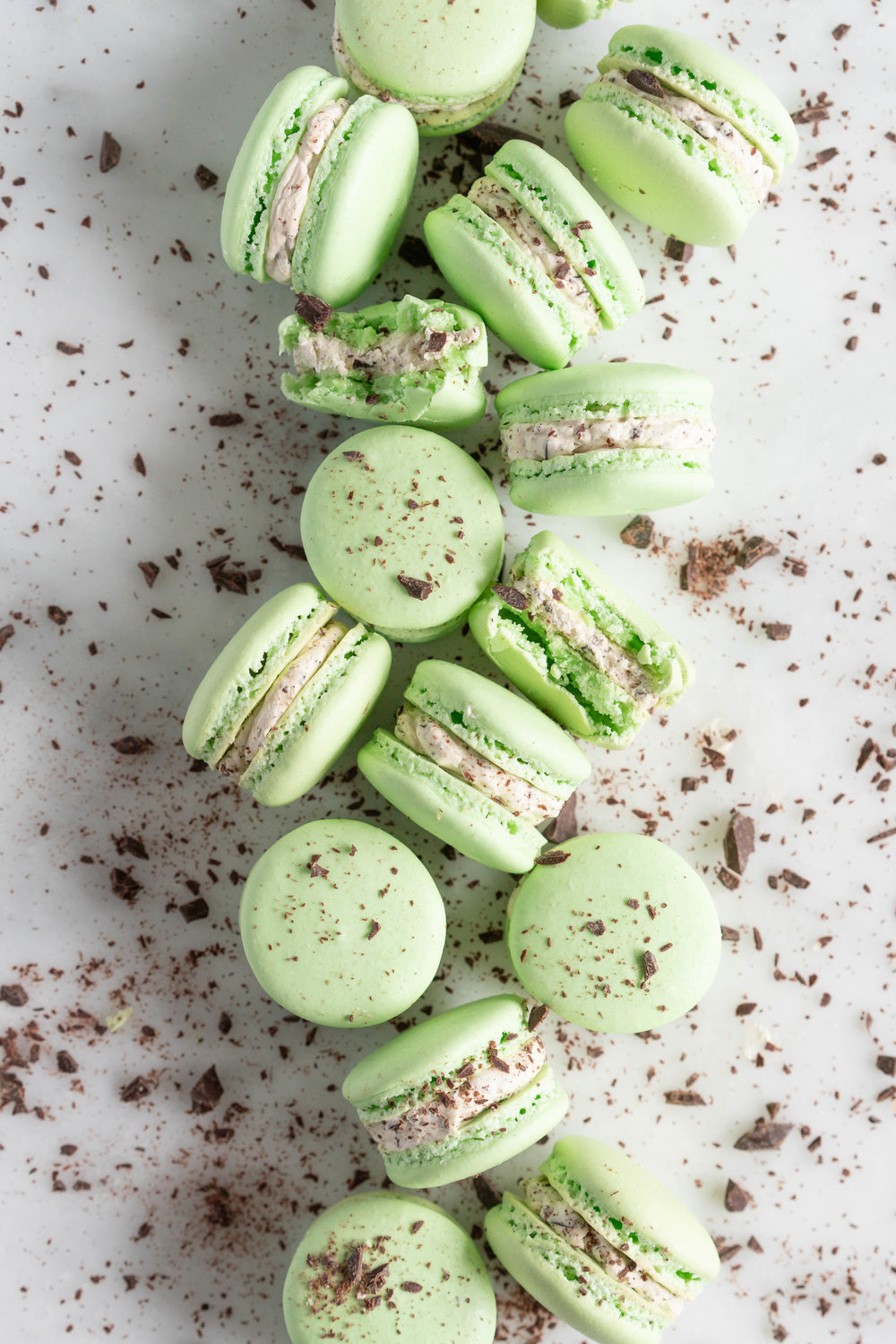 Mint Chocolate Chip Macarons with German buttercream. Delicate French macaron shells are sandwiched together by a mint chocolate chip german buttercream that tastes just like ice cream! #mintchocolatechip #mintchip #frenchmacarons #macarons #recipe #howtomake