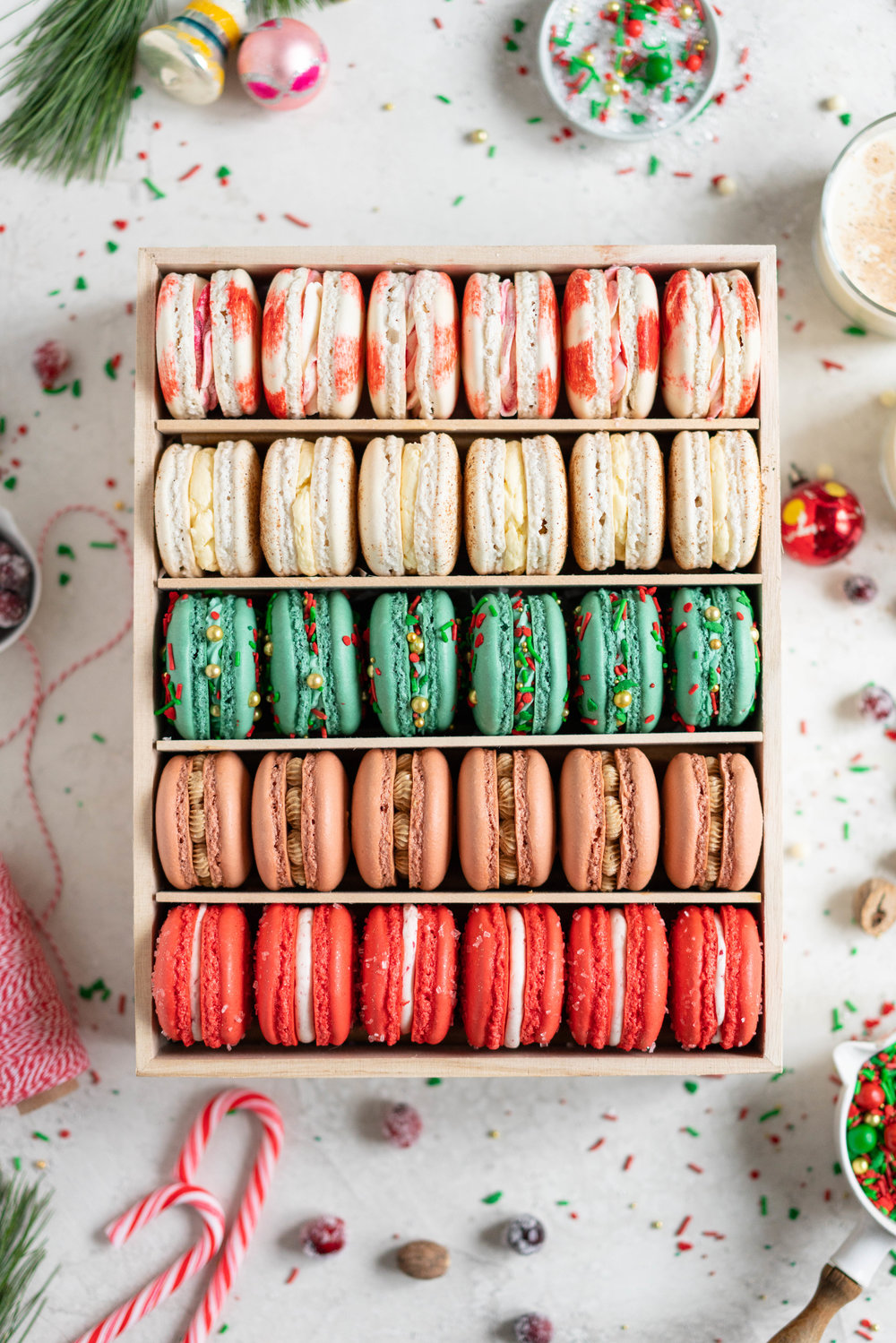 The Ultimate Christmas Macaron box - a cute, gluten free twist on the traditional cookie box. This cookie box is filled with the flavours of christmas - Candy Cane, Eggnog, Christmasfetti, Gingerbread, and cranberry. Each macaron is filled with a delicious complementary filling - ranging from american buttercream to German buttercream. This macaron box would make the perfect homemade gift. Grab the recipes now!