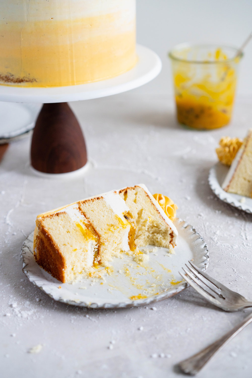 Vanilla Layer Cake with Passionfruit Curd and Vanilla Swiss Meringue Buttercream. Perfect for any occasion - layers of vanilla cake are sandwiched with a silky vanilla bean swiss meringue buttercream, and filled with a tangy, creamy passionfruit curd. #layercake #passionfruitcake