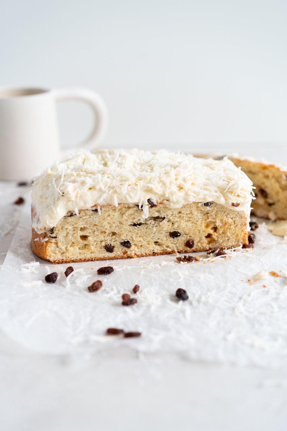 Boston Bun is a raisin brioche bun, covered with vanilla icing, and finished with shredded coconut. It is super easy to make, requires no fancy equipment or dough twisting, and makes the perfect treat with a cup of coffee or to entertain guests. #bostonbun #sallylunn #raisinbrioche