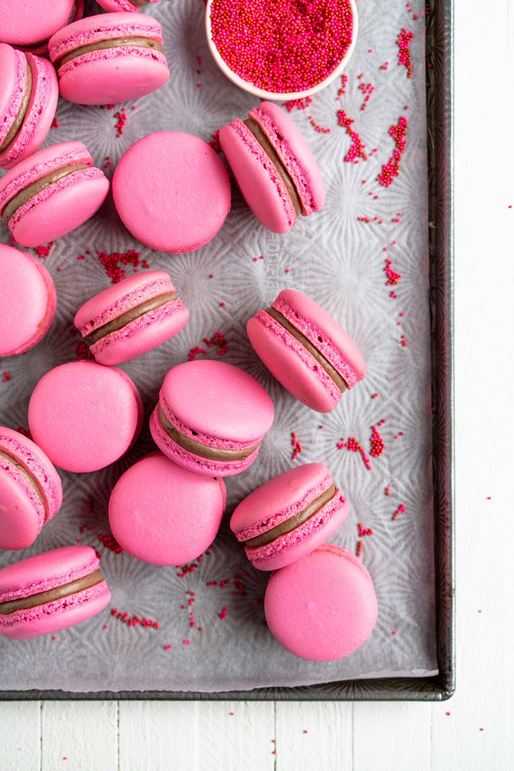 Raspberry and Dark Chocolate Macarons - A classic pink shell, filled with a homemade raspberry quick jam, and a silky Dark chocolate swiss meringue buttercream, deepened with a little black cocoa. These are a classic valentine's day pairing, and would be perfect as a gift, but would also make an amazing anytime treat for a chocolate or berry lover. #frenchmacaron #valentinesmacaron